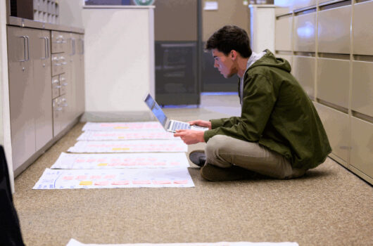 Student researcher with laptop surrounded by posters